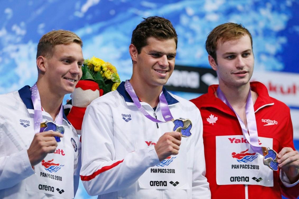 De gauche à droite : le médaillé d'argent Caeleb Dressel, des États-Unis, le médaillé d'or Michael Andrew, des États-Unis, et le médaillé de bronze canadien Yuri Kisil, aux Championnats pan-pacifiques à Tokyo, le 12 août 2018. AP Photo/Koji Sasahara