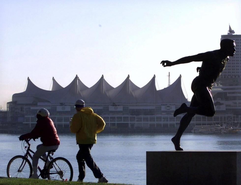 Un cycliste et un joggeur parcourent la digue du parc Stanley à Vancouver devant la statue de Harry Jerome.