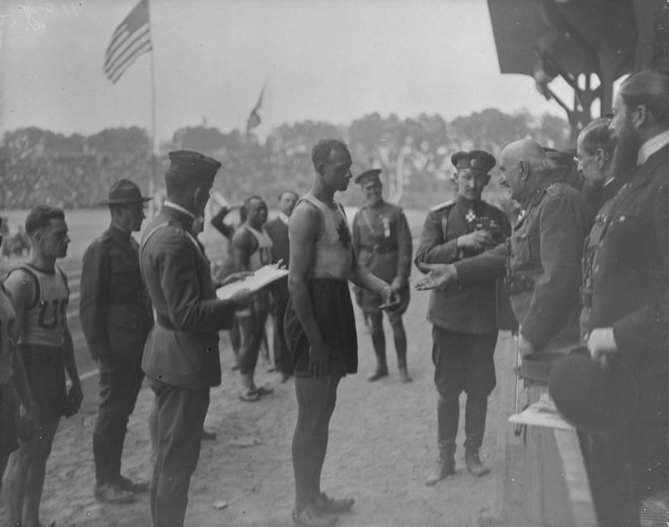 Le roi du Monténégro tend la main vers Army Howard en bordure de la piste d'athlétisme.