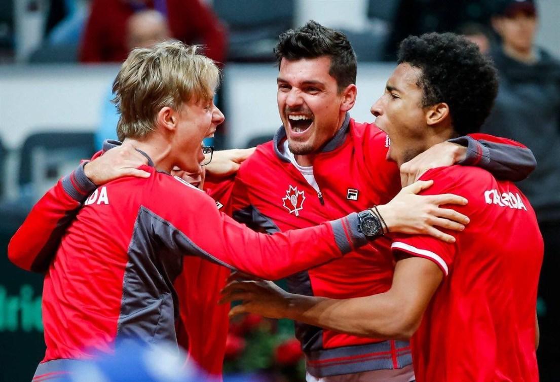 Trois joueurs de tennis se donnent une accolade.