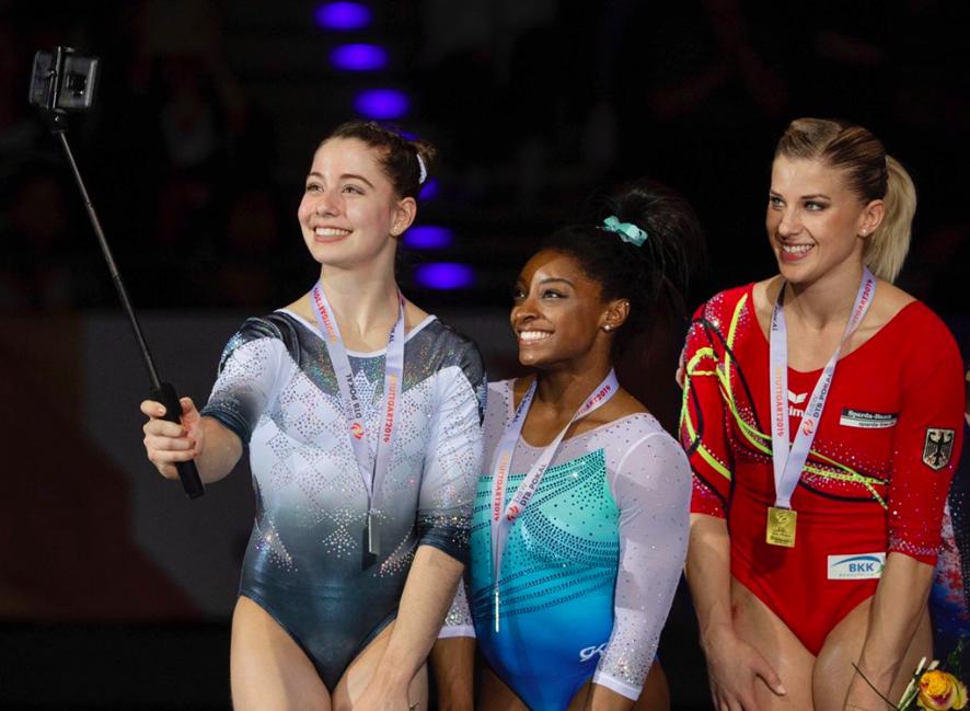 Padurariu prend un égoportrait avec deux autres gymnastes à l'aide du bâton à selfie.