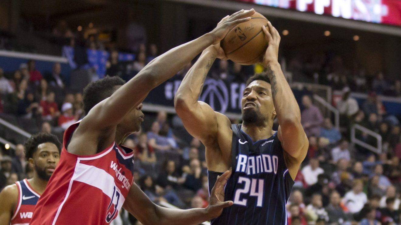 Le joueur de centre du Magic d'Orlando est sur le point de lancer le ballon devant un joueur des Wizards lors d'un match de la NBA à Washington.