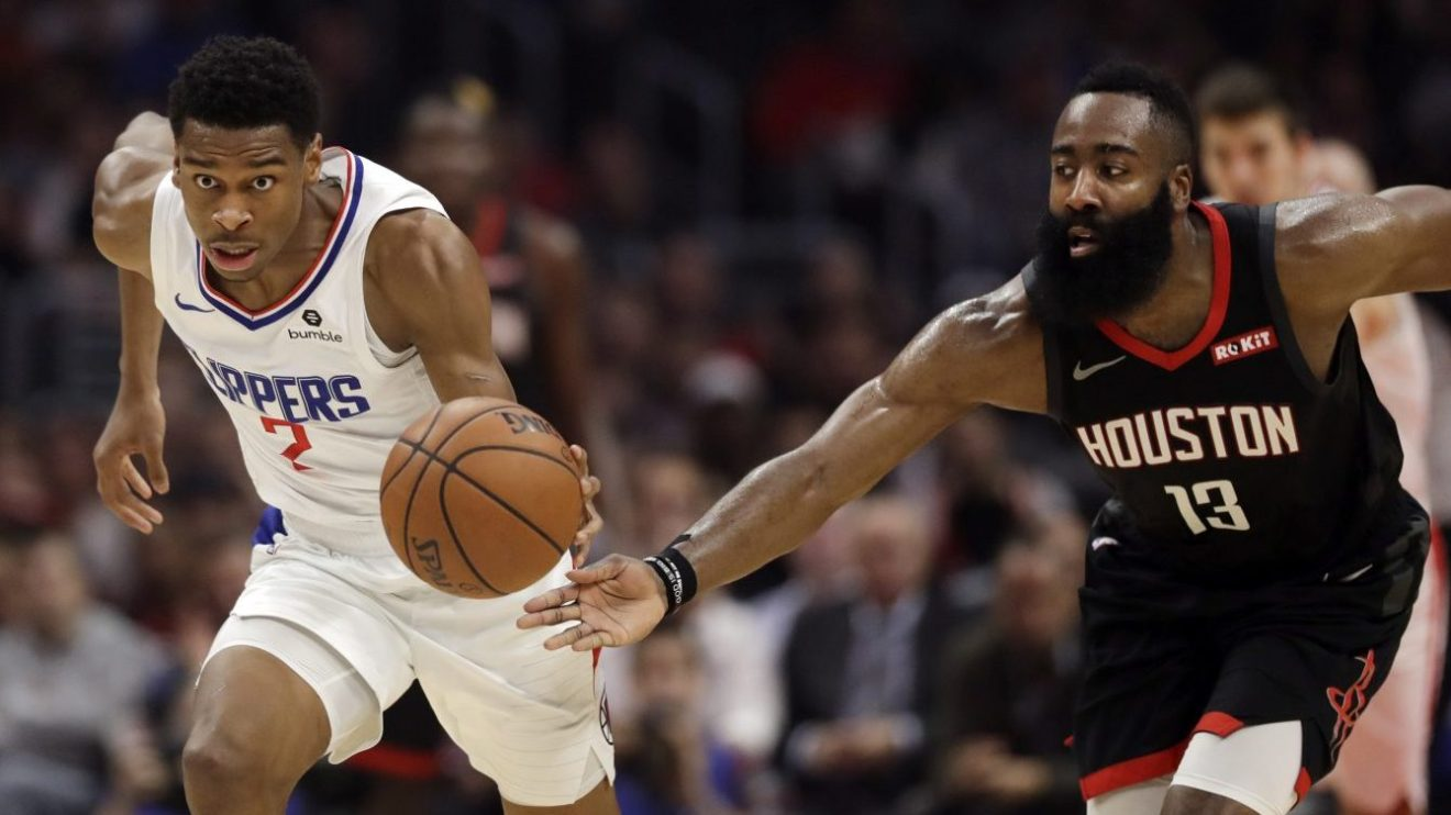 Shai Gilgeous-Alexander des Clippers de Los Angeles dribble devant James Harden lors d'un match de la NBA.