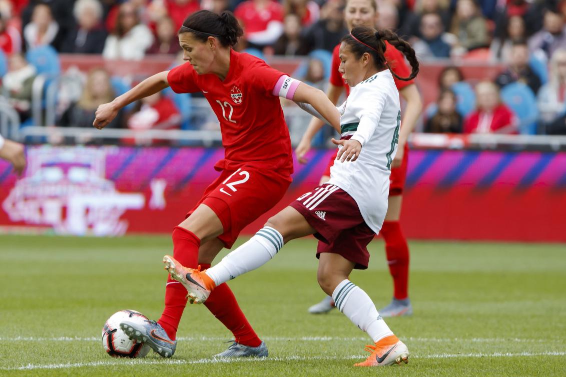 Deux joueuses de soccer luttent pour le ballon.