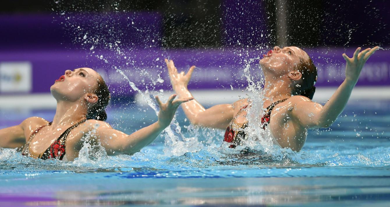 Jacqueline Simoneau et Claudia Holzner dans la piscine, regardant vers le ciel.
