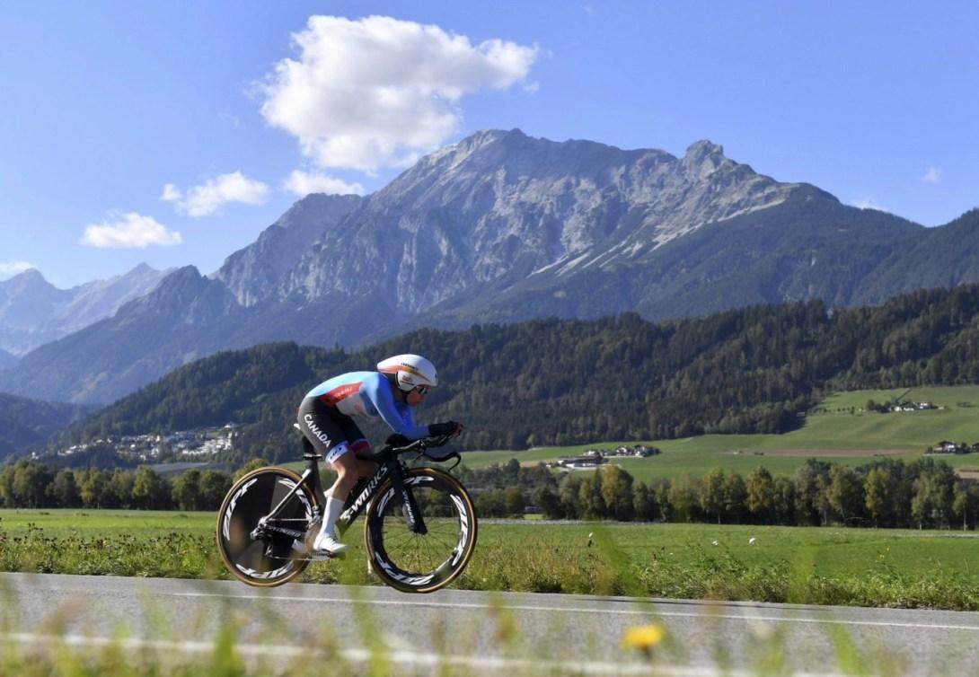 Une cycliste canadienne sur route, avec un magnifique paysage montagneux en arrière-plan.