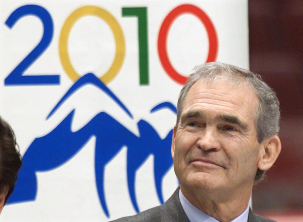 Jack Poole pose devant le logo des Jeux de Vancouver 2010
