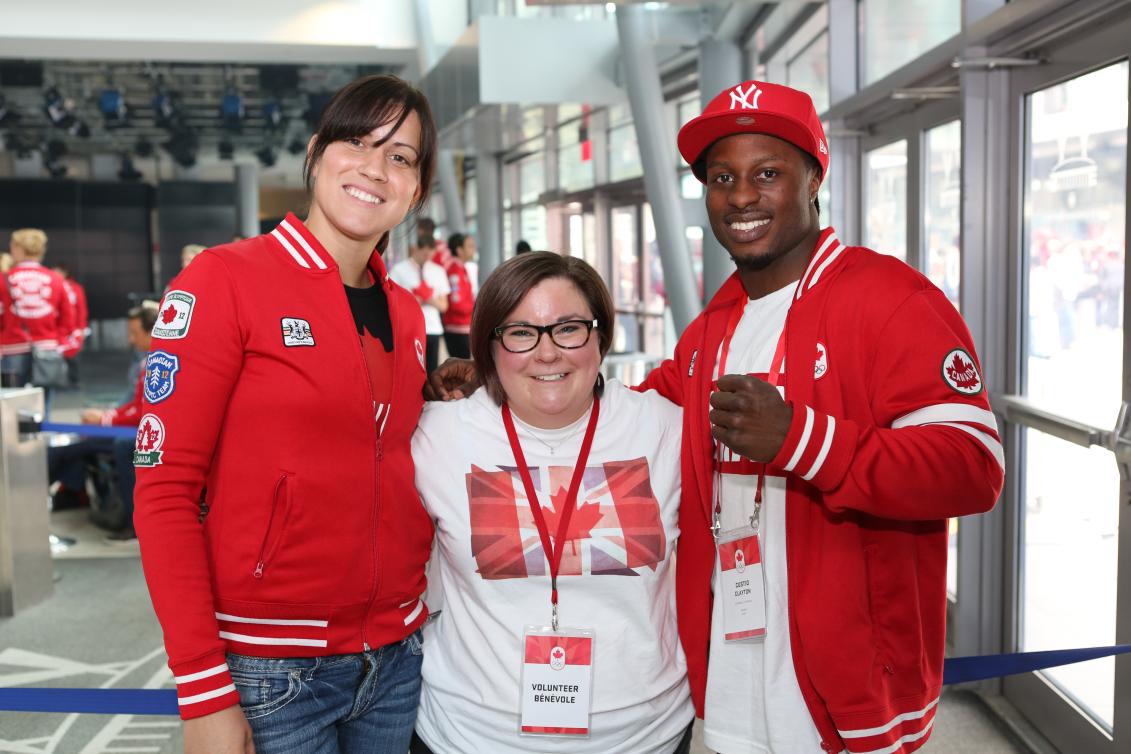 Deux athlètes et une bénévole se serrent et sourient à la caméra