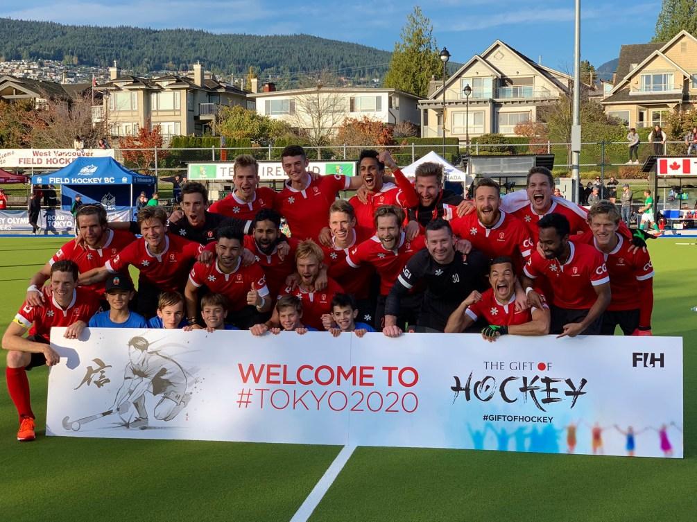 L'équipe de hockey sur gazon pose avec la banderole de qualification olympique