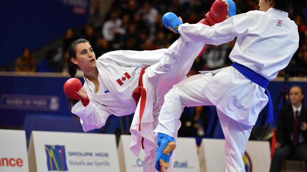 Une athlète de karaté donne un coup de pied à son adversaire.