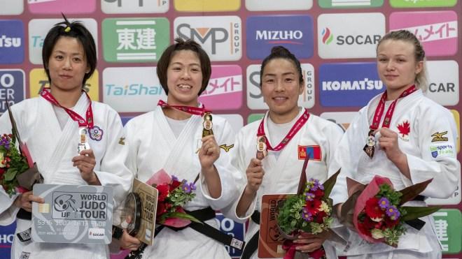 Les quatre médaillées posent sur le podium avec leurs médailles
