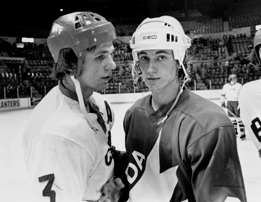 Wayne Gretzky regarde la caméra, accompagné d'un joueur russe