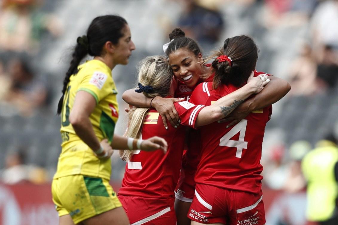 Trois joueuses canadiennes se font un câlin pour célébrer un point.
