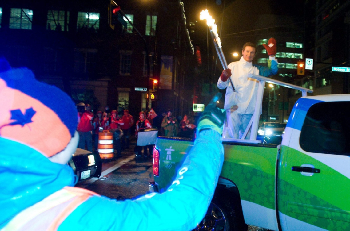 Wayne Gretzky tient la flamme olympique à bord d'une voiture.