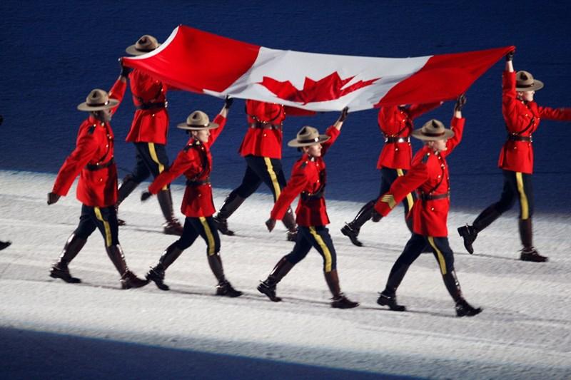 Huit soldats de la GRC portent le drapeau canadien.