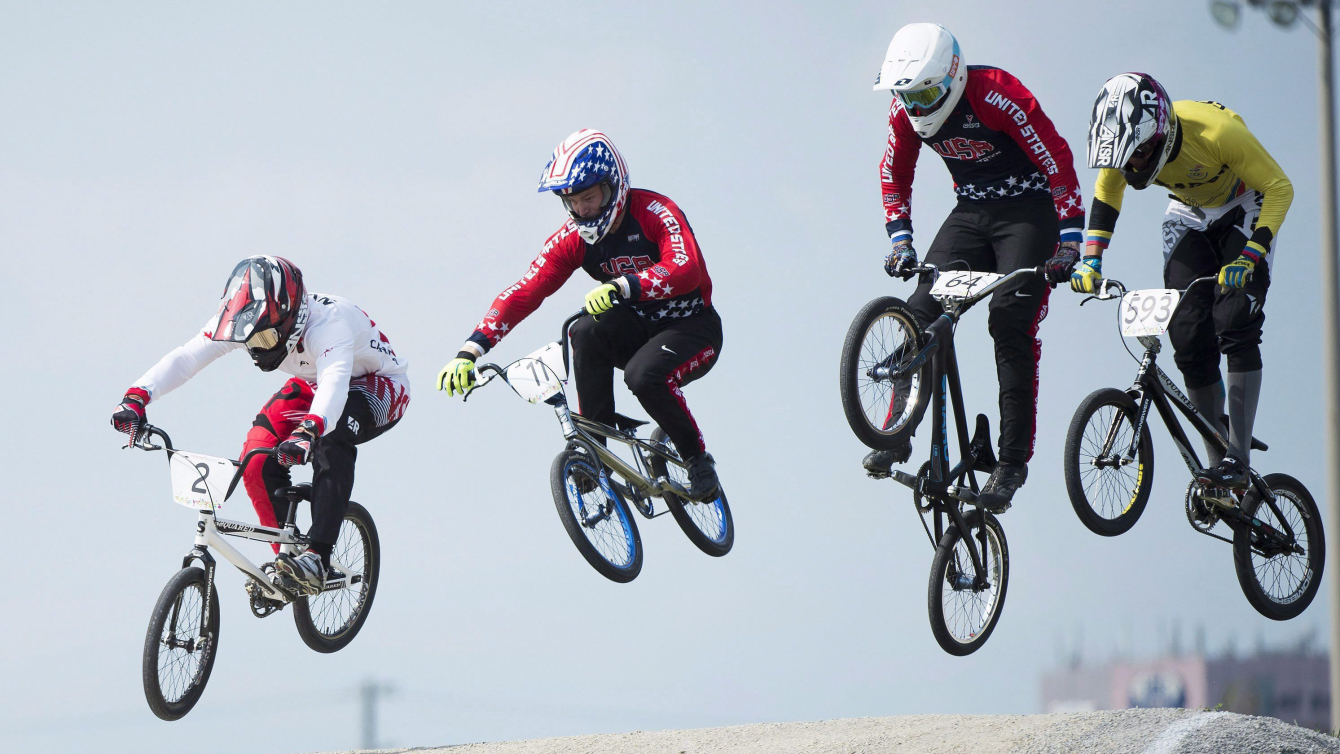Quatre cyclistes de BMX en suspension dans les airs après un saut