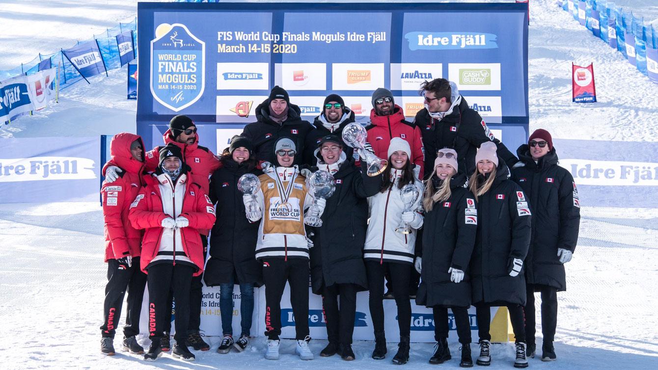 Les athlètes de bosses d'Équipe Canada pose devant une banderolle