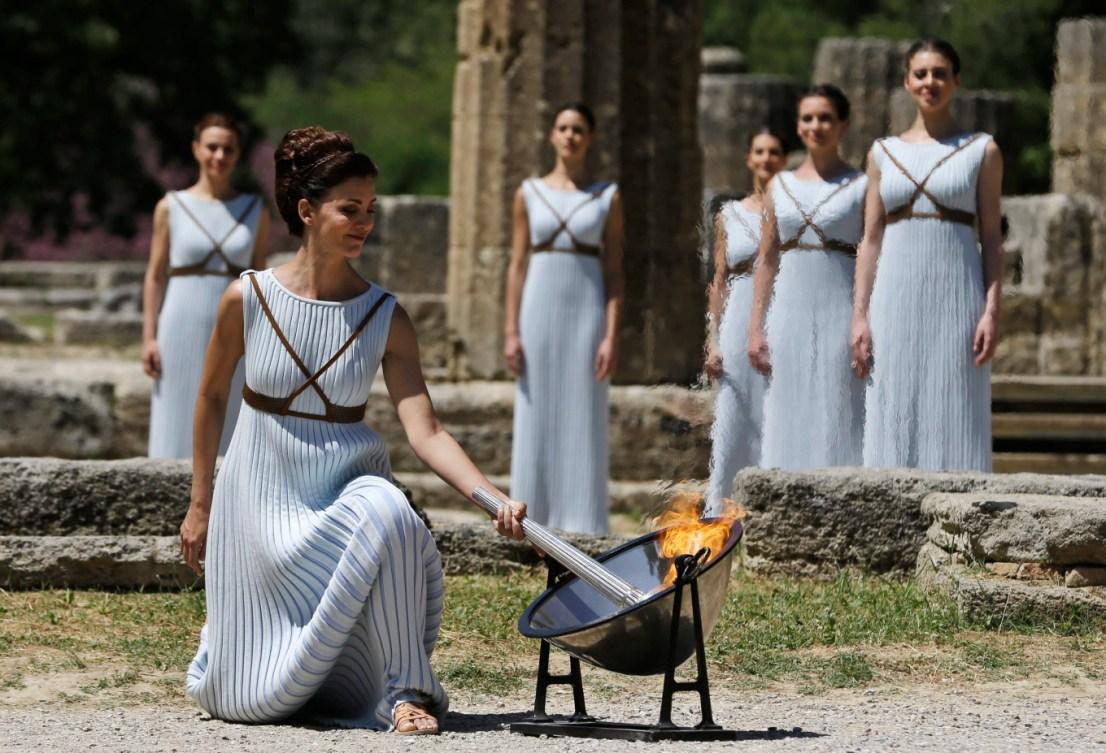 Une femme en robe blanche allume la flamme dans un décor de la Grèce antique