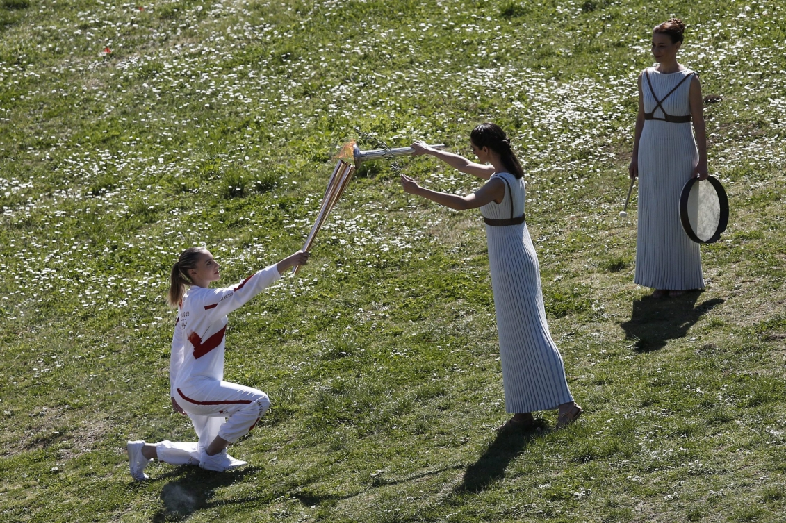 Une femme à genou tient la flamme pendant qu'une femme debout l'allume